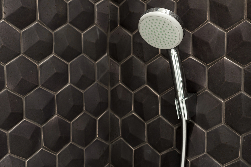 Close up of new rain shower head in the bathroom against a background of black tiles