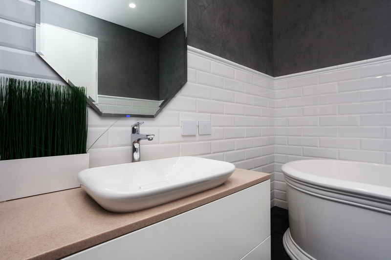 Bathroom interior. Bright bathroom with new tiles. New washbasin, white sink and large mirror