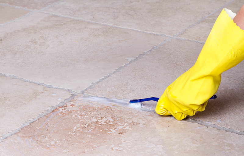 cleaning the floor tile grout with a toothbrush and wearing yellow gloves