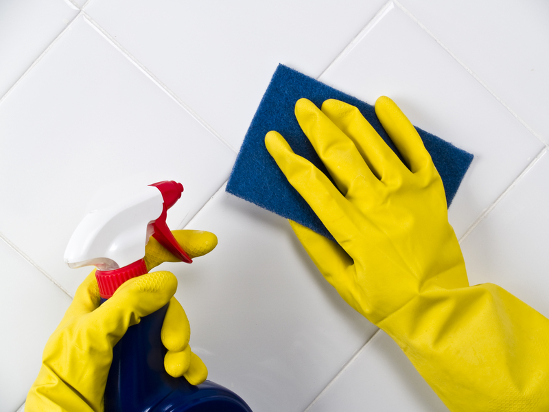 cleaning the tile grout with a sponge and cleaning spray
