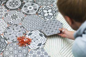man laying bold floor tiles